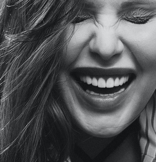 Crno bela fotografija devojke koja se smeje