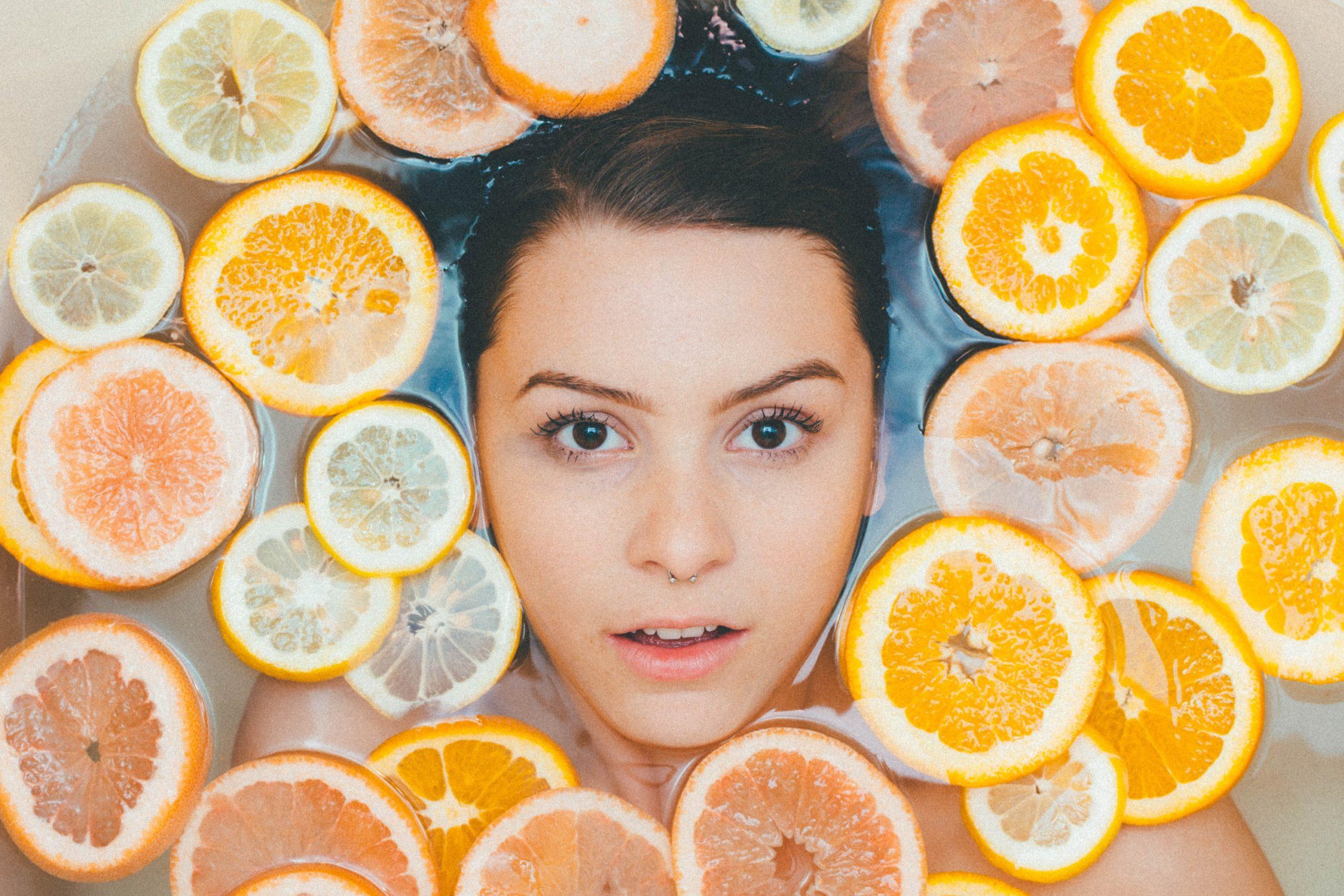 Glava devojke u vodi pored kolutova pomorandže