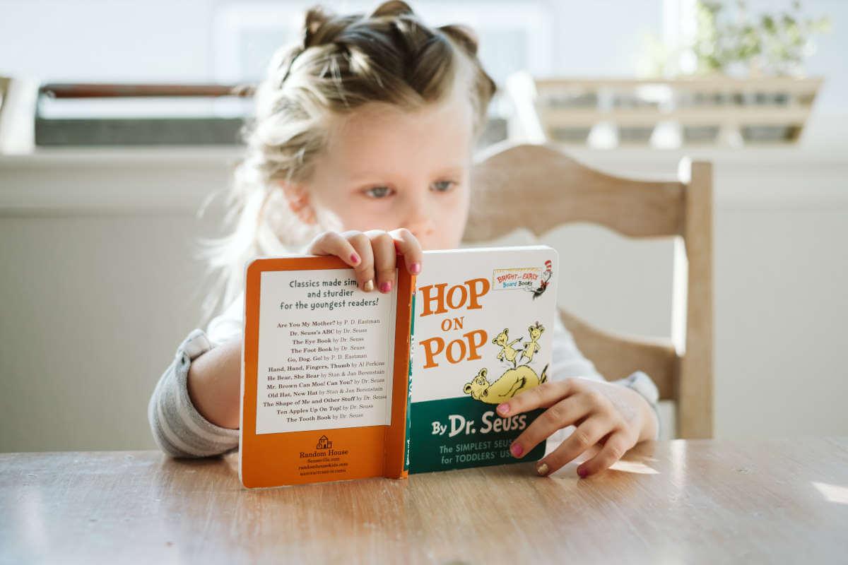 Devojčica čita knjigu za stolom
