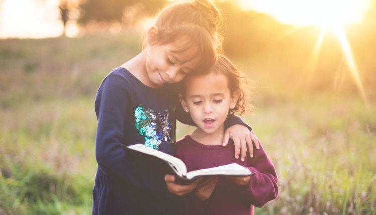Dve devojčice čitaju knjigu u prirodi