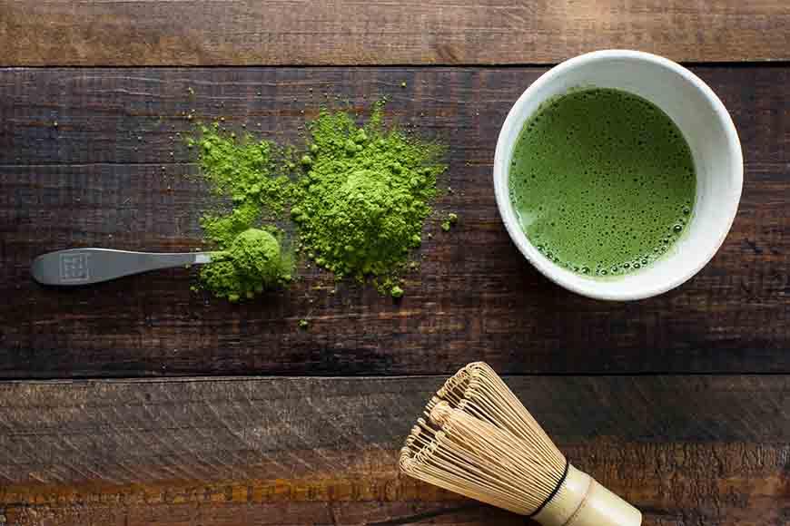 Šolja zelenog čaja na stolu sa ekstraktom zelenog čaja pored šolje