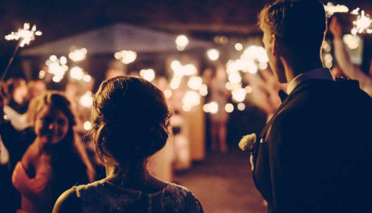 Mlada i mladoženja ispred gostiju koji drže prskalice
