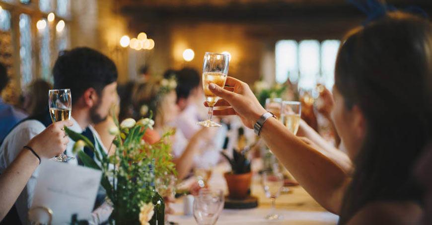 Gosti dižu čaše i nazdravljaju mladencima