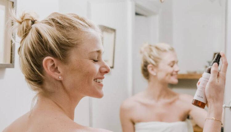 Nasmejana devojka plave u kupatilu ispred ogledala