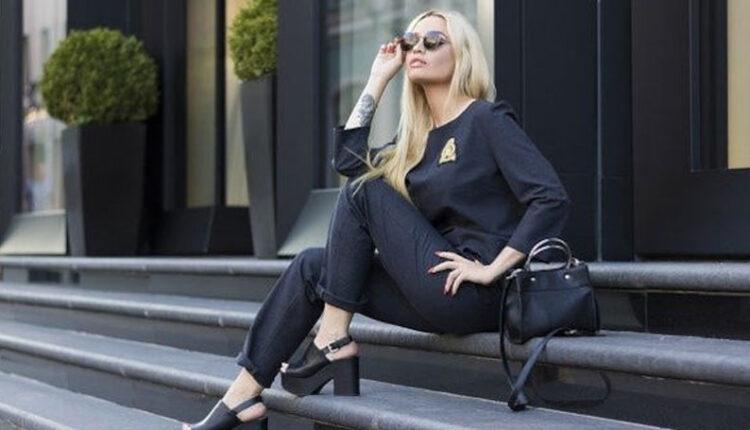 Žena odevena u crnu kombinaciju sa naočarima sedi na stepenicama