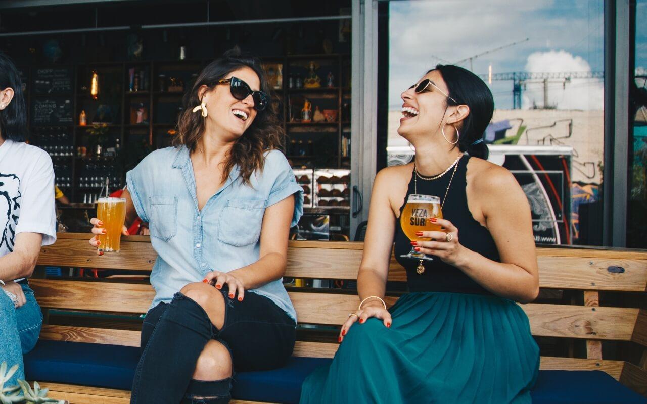 Dve nasmejane devojke sede na klupici i piju pivo