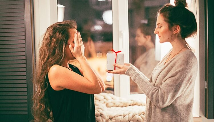 Devojka u sivom džemperu daruje poklon drugarici u crnoj majici dok su joj rukama prekrivene oči