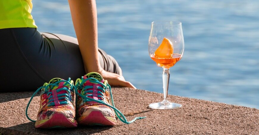 devojka sedi na betonu a pored nje patike i piće