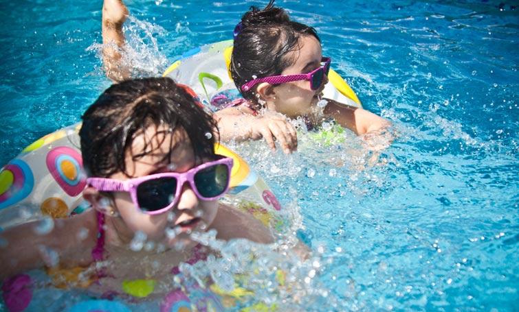 Dva mališana plivaju u bazenu sa naočarima i gumama za plivanje