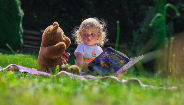 dete i plišani meda u travi